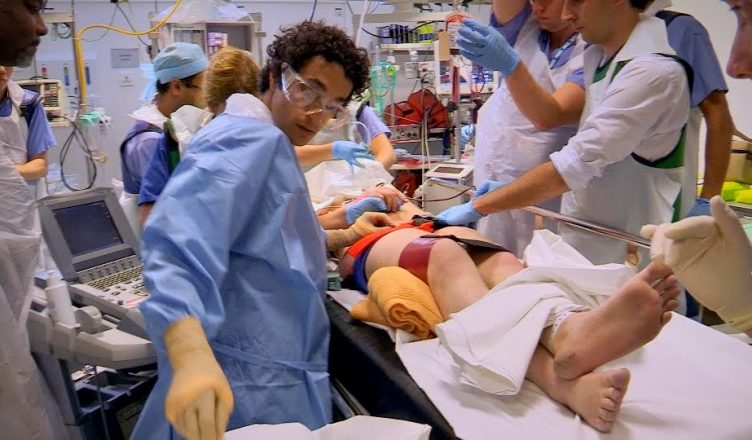 Photo 1: Royal London Hospital medics assess Michael's injuries with Air Ambulance paramedic Ben Macauley pictured in red.